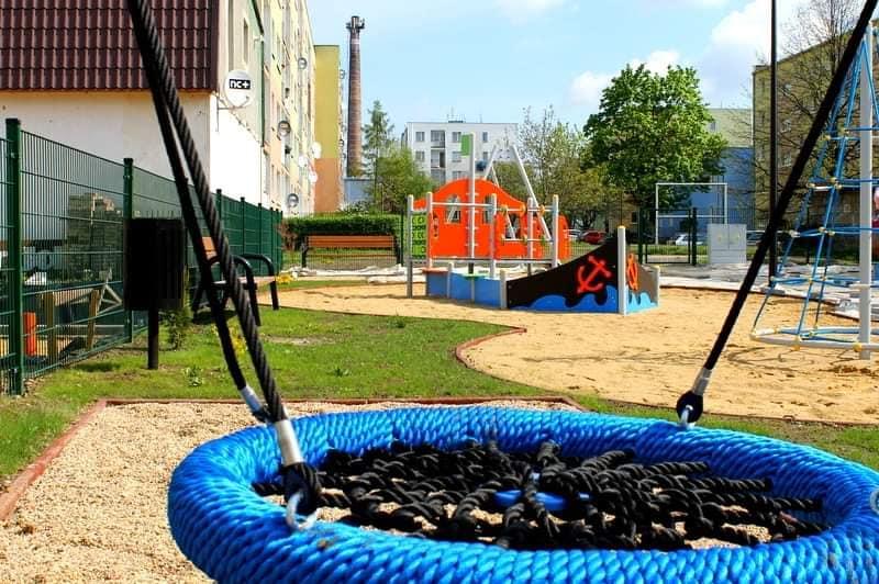 Widok placu zabaw dla dzieci, ookoła bloki osiedlowe